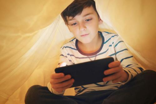 kid under covers on phone